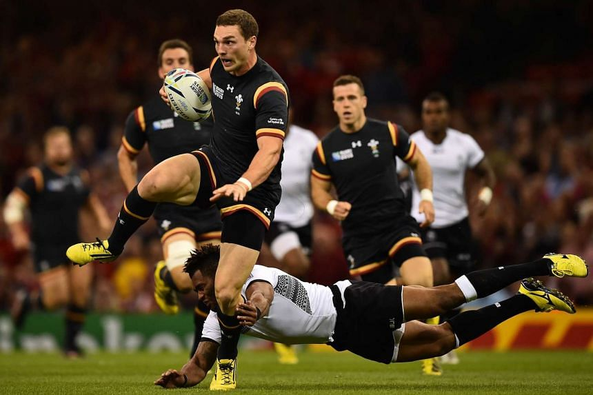 Wales' wing George North (left) is tackled by Fiji's full-back Metuisela Talebula.