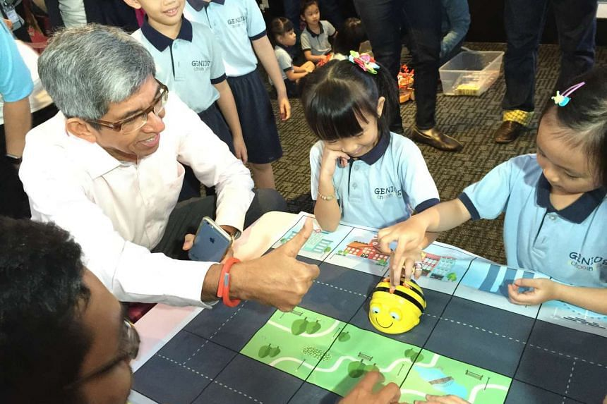 Minister for Communications and Information Dr Yaacob Ibrahim interacting with preschoolers at the IExperience centre. BeeBot, a bright yellow robot that teaches children problem-solving, logical thinking and teamwork, is one of the items showcased