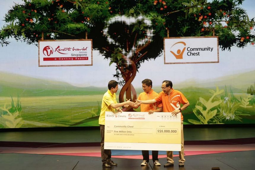 Resorts World Sentosa chairman and CEO Tan Hee Teck (left) presents a cheque of $5 million to Community Chest chairman Philip Tan (right) and witnessed by Minister for Social and Family Development Tan Chuan-Jin (centre) at the first Sharity Day crea