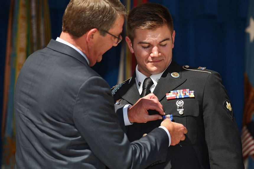US Defense Secretary Ashton Carter (left) pins the Solider's Medal on Army Specialist Alek Skarlatos during an awards ceremony on Sept 17, 2015 for Skarlatos and two other men who helped stop a gunman on a Paris-bound train.