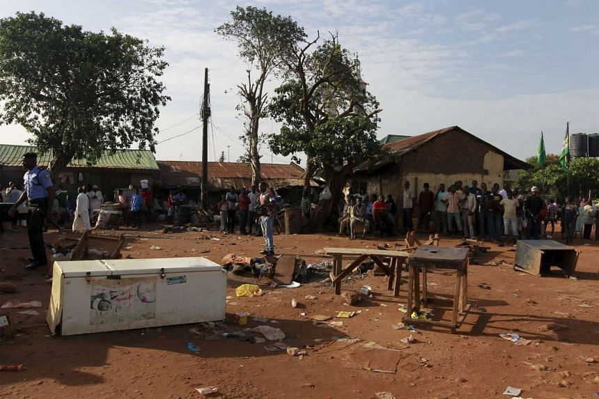 People gather at the scene of a bomb blast in Nyanya, on the outskirts of Abuja, Nigeria, Oct 3, 2015.