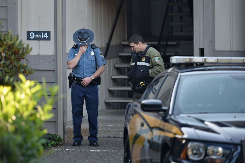 Police officers stand guard outside the apartment building where alleged gunman Chris Harper Mercer lived in Roseburg, Oregon.