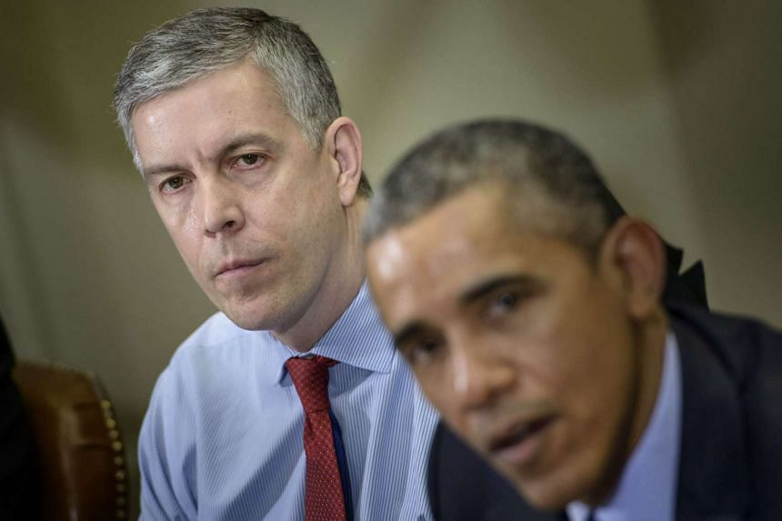 A March 2015 photo shows Duncan (left) listening to Obama at a press briefing.