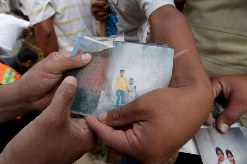 Residents show a photograph of two missing children at the site of a mudslide in Santa Catarina Pinula, on the outskirts of Guatemala City, on Oct 2, 2015.