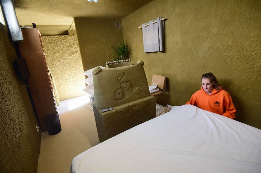 """An employee preparing the bedroom at the """"sandcastle hotel"""" on Oct 2, 2015."""