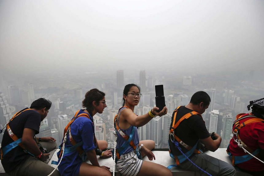 A woman (centre) takes a selfie against the skyline of the capital shrouded in a thick haze, Kuala Lumpur, Malaysia, on Oct 2, 2015.