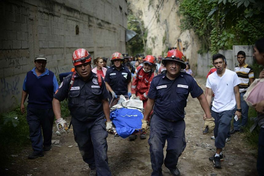 Rescuers carry a victim after a landslide at Cambray village, in Santa Catarina Pinula municipality.