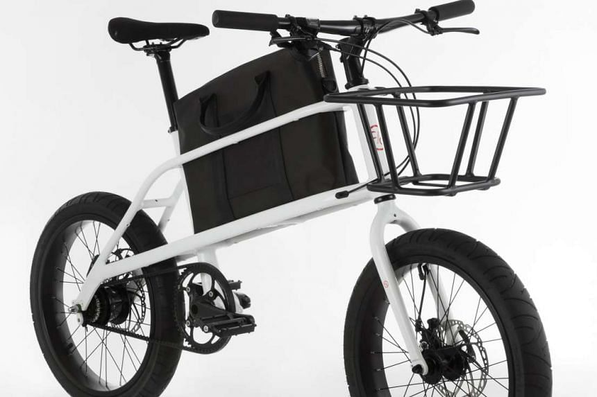 The Quinn is a compact cargo bicycle that lets the rider carry a bag in a storage compartment between the wheels.