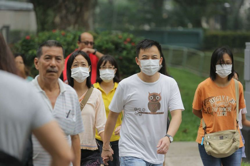 Singaporeans wearing masks crossing the road along Commonwealth Drive at 10.45am on Oct 3, 2015.