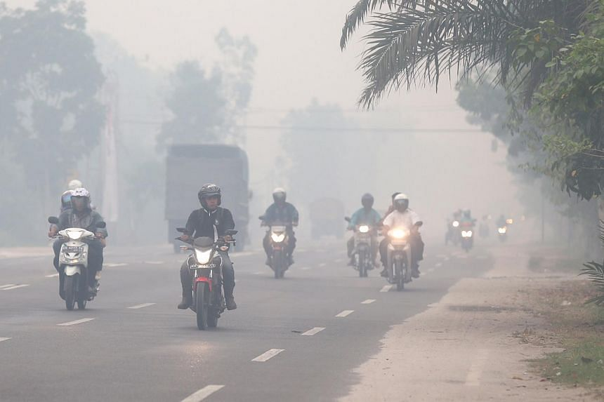 Motorists turning on their headlights even after sunrise as the thick haze fills the air in Palangkaraya, Central Kalimantan, on Oct 1, 2015.