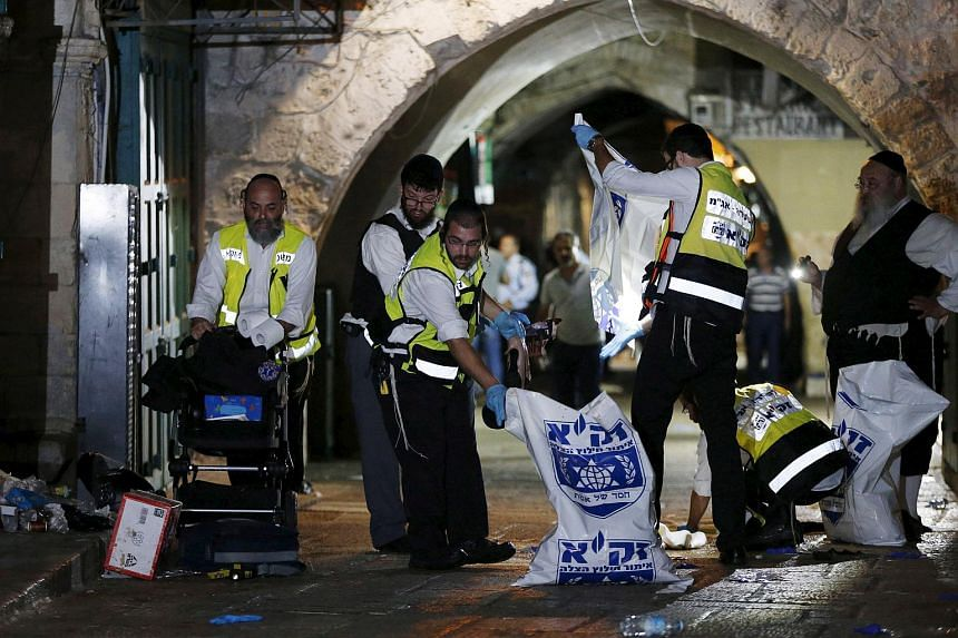 Members of the Zaka Rescue and Recovery team clean the scene where a Palestinian was shot dead after he stabbed and killed two people in Jerusalem's Old City on Oct 3, 2015.