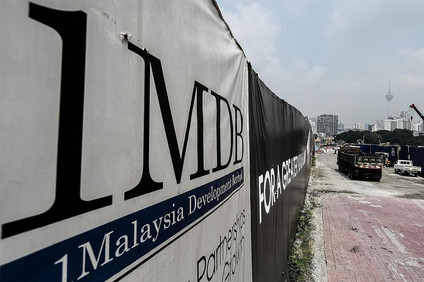 Trucks driving past a billboard with the 1MDB logo at the funds flagship Tun Razak Exchange construction site in Kuala Lumpur.