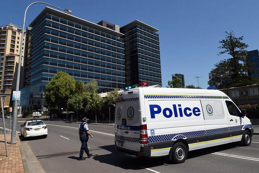 Police blocking off the scene near New South Wales Police Headquarters where a 15-year-old gunman shot dead a civilian police employee the previous day, before being gunned down by police, on Oct 3, 2015.