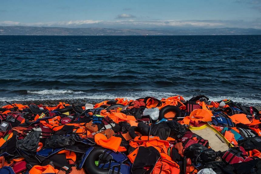 Life jackets and inflatable rubber dinghies allegedly used by refugees to cross the Mediterranean Sea lie on the shore at a beach near Skala Sikaminias, Lesbos island, Greece, on Oct 2, 2015.