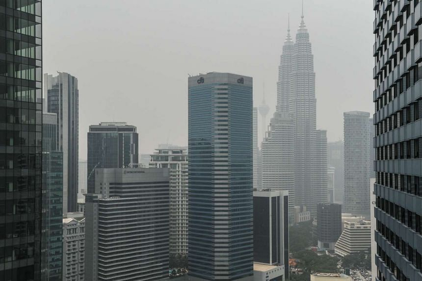 Malaysia's Petronas Twin Towers (centre right) are seen shrouded in haze in Kuala Lumpur on Sept 29, 2015.