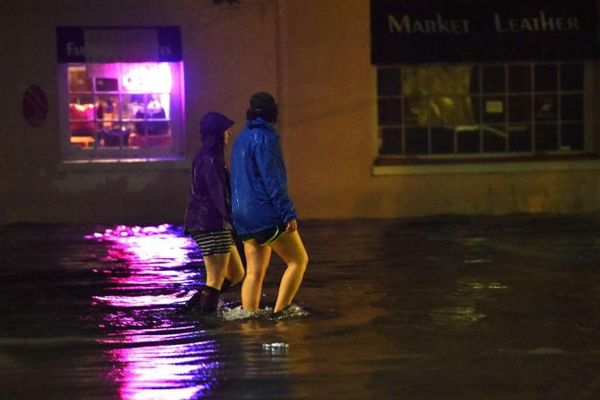 Two women walk across a flooded street in downtown Charleston, South Carolina, on Oct 3, 2015.