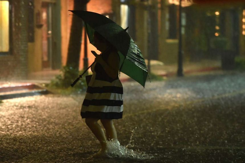 A woman with an umbrella crosses a flooded street in downtown Charleston, South Carolina, on Oct 3, 2015.