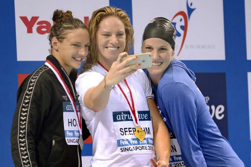 Australia's Emily Seebohm (centre) posing for a selfie after winning the gold in the women's 100m backstroke with silver medallist Katinka Hosszu of Hungary (left) and bronze medallist Missy Franklin of the US (right), at the OCBC Aquatic Centre on O