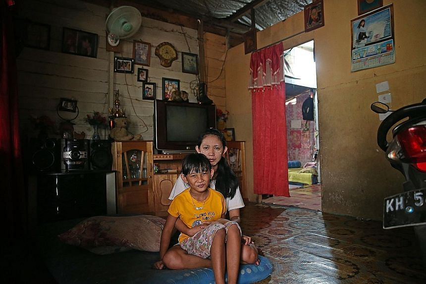 Ms Gayantri, 27, and her seven-year-old daughter Keyla Sari in their house in Palangkaraya, Central Kalimantan. The divorcee, who also lives with her mother, has tried her best to keep the haze out of the house. The family bought a second fan and clo