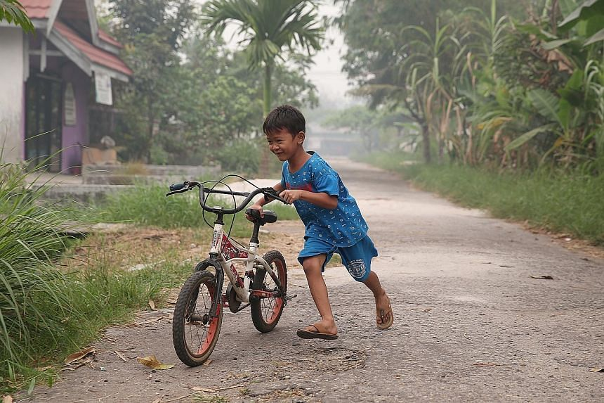 A boy playing on the road despite the air pollution in Palangkaraya, Central Kalimantan, last Thursday.