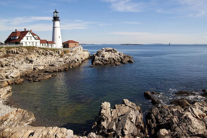 "The riot of autumn colours (left) in Maine draws ""leaf peepers"", or people who travel there for the scenery. The historic Portland Head Lighthouse (far left) at the jagged shores of Fort Williams Park, Cape Elizabeth. A house swaddled with vibrant ci"