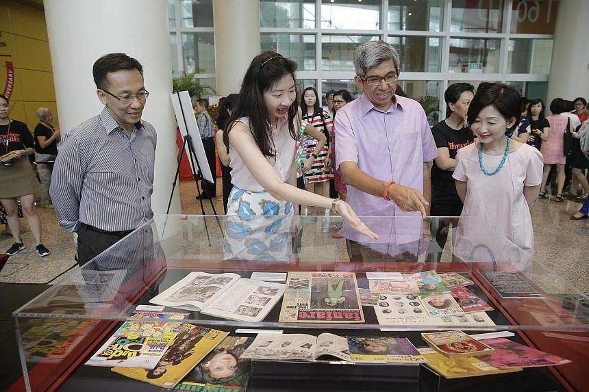 Dr Yaacob Ibrahim viewing a collection at the display to mark the NLB's 20th anniversary at the National Library Building yesterday, with (from left) NLB chairman Chan Heng Kee, assistant director for content and services Alicia Yeo, and chief execut