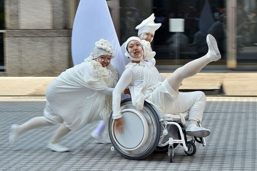 Dancers performing on a prototype of an electric wheelchair, dubbed the &Y01 or Andy 01, at a Slow Movement event in Tokyo. Japan's musical instruments conglomerate Yamaha and motorcycle giant Yamaha Motor produced the wheelchair, which plays music f