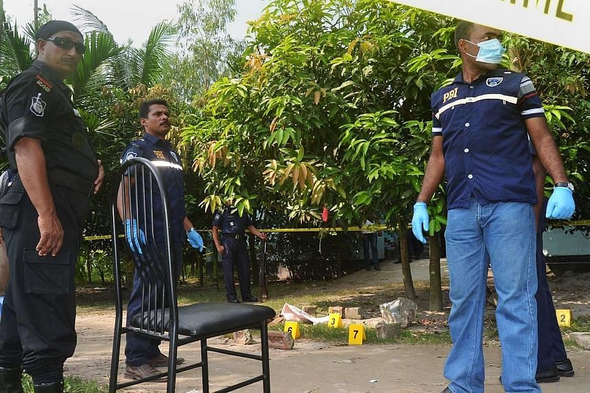 Police officers standing guard at the site where a Japanese citizen was killed by masked men in Rangpur.