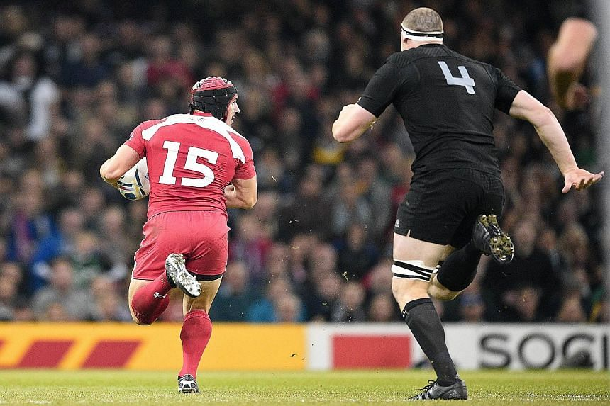 Georgia's full-back Beka Tsiklauri (left) can't be caught as he scores his team's first try against New Zealand. Georgia exposed some shortcomings in the defending champions and a win in their next game against Namibia will earn the Europeans a slot