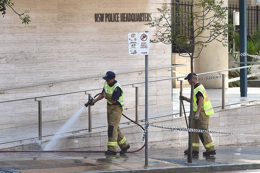 A fireman yesterday hosing down the scene where a 15-year-old boy shot dead a civilian police employee last Friday, before being gunned down by police, in Sydney.