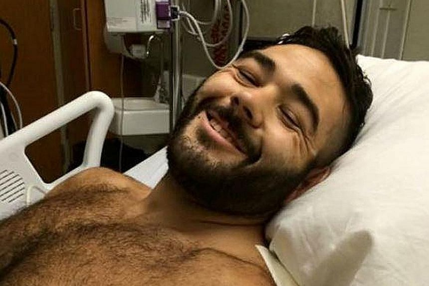 Mr Chris Mintz, who was shot seven times while trying to stop the gunman, recovering in hospital.