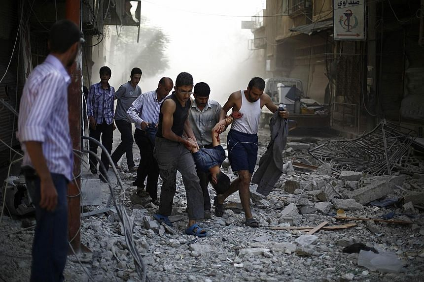 Syrians evacuating a wounded man following air strikes by Syrian government forces on the rebel-held town of Douma, east of the Syrian capital Damascus, last Friday.
