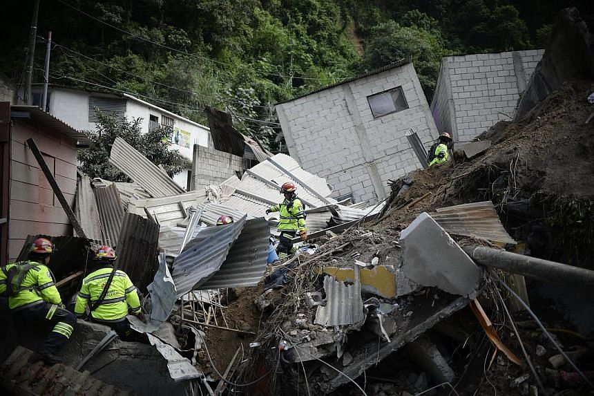 Rescuers searching for victims among wrecked homes after the landslide at El Cambray II village in Guatemala.