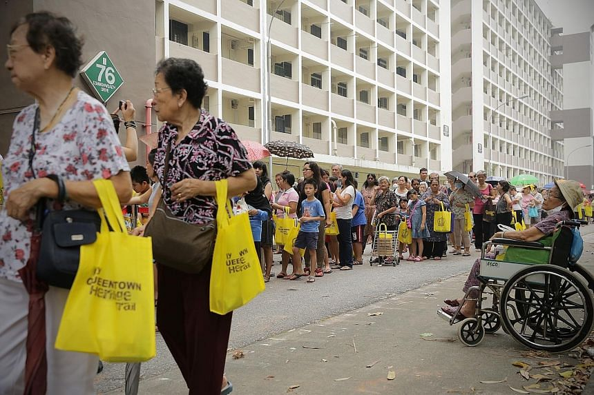 People queuing for ice-cream yesterday at the farewell carnival giving former residents of Blocks 74 to 80, Commonwealth Drive, a chance to say goodbye to their former estate. The blocks will be demolished next month for redevelopment.
