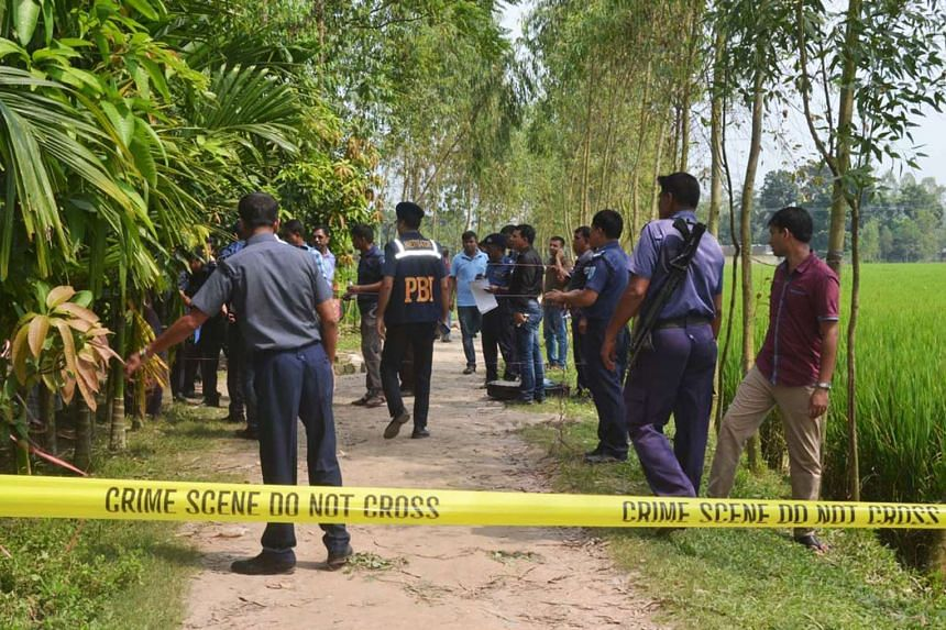 Bangladeshi police officials stand guard at the site where a Japanese citizen was shot to death by attackers in Rangpur.