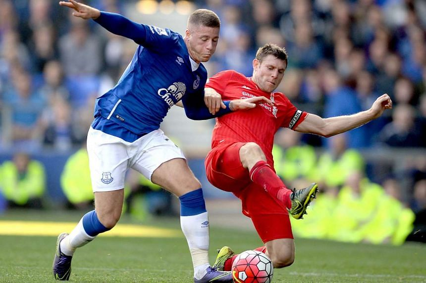 Everton's Ross Barkley (left) and Liverpool's James Milner tussle for the ball during their English Premier League soccer match at Goodison Park, in Liverpool, on Oct 4, 2015.