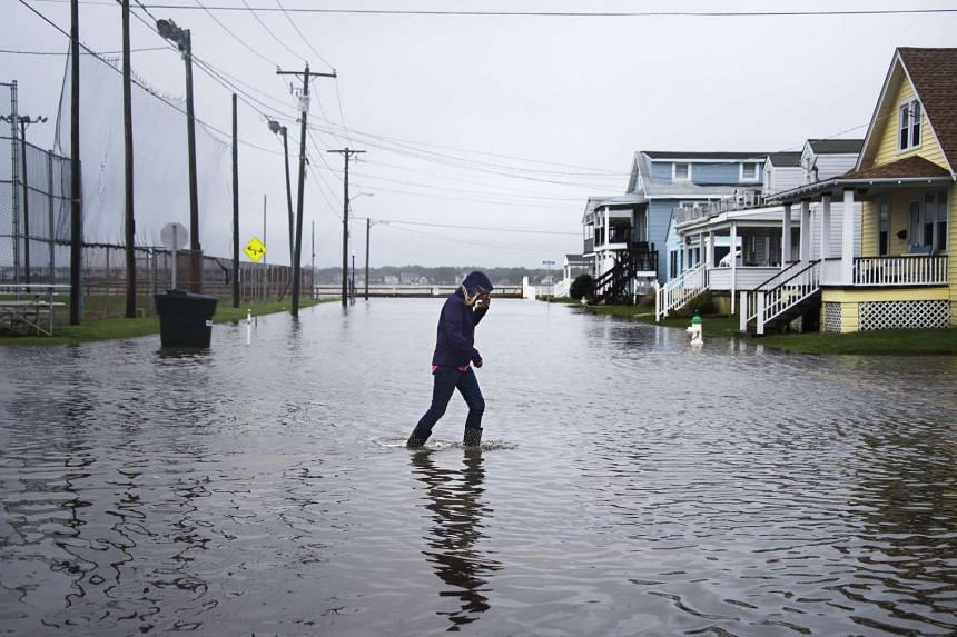 A woman crosses a flooded street in Ocean City, Maryland, on Oct 3, 2015.
