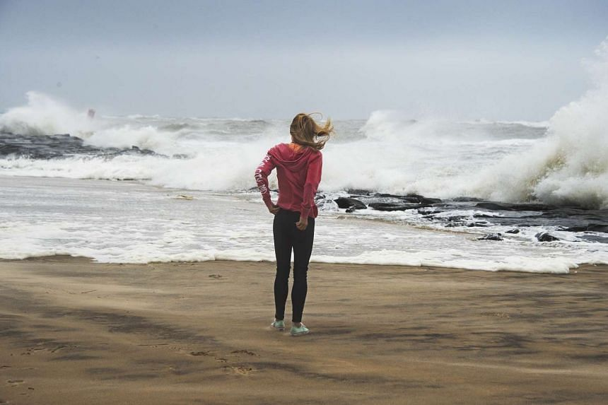 A tourist watches as waves batter the beach in Ocean City, Maryland, on Oct 3, 2015.