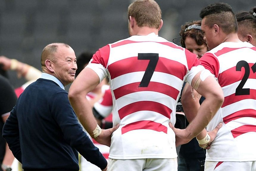 Japan's head coach Eddie Jones (left) with his players after Japan won their Pool B match against Samoa.