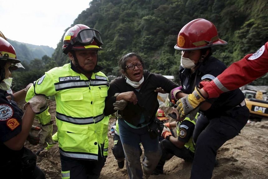Rescue team members helping a woman after recovering the bodies of her relatives at an area affected by mudslide in Guatemala City, on Oct 3, 2015.