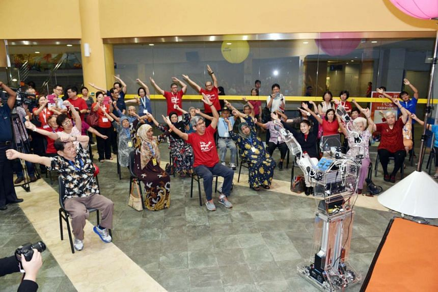 Dr Yaacob (centre) joins seniors in taking cues from the Robocoach at the Silver IT Fest at Nanyang Polytechnic yesterday.  PHOTO: INFOCOMM DEVELOPMENT AUTHORITY