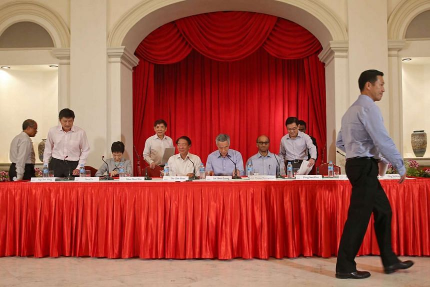 Prime Minister Lee Hsien Loong, flanked by Deputy Prime Ministers Teo Chee Hean and Tharman Shanmugaratnam, at a press conference to unveil the new Cabinet line-up at the Istana last Monday. Taking their seats were other office-holders (from left) Ma