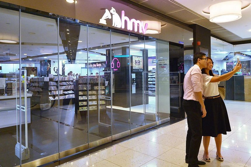 A couple taking a photo of themselves on Sept 30, 2015, in front of the HMV store at Marina Square before it closes its doors for the last time.