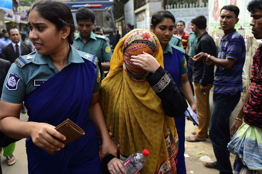 Bangladeshi security personnel escort Nritto Shahadat, the wife of Shahadat Hossain, towards a court appearance after her arrest in Dhaka on Oct 4, 2015. Bangladesh police arrested international cricketer Shahadat Hossain's wife over allegations of b