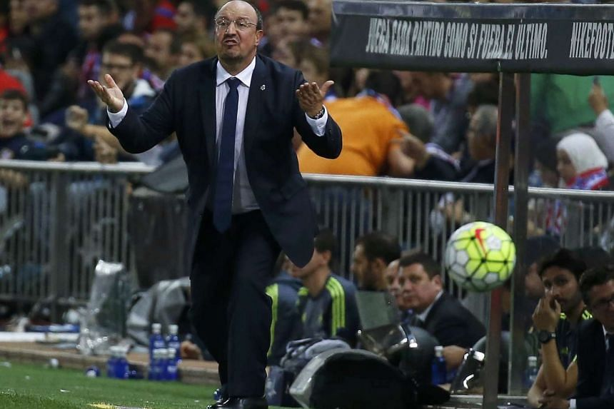 Read Madrid coach Rafa Benitez gesturing to his players by the sidelines during the league match against Atletico Madrid.