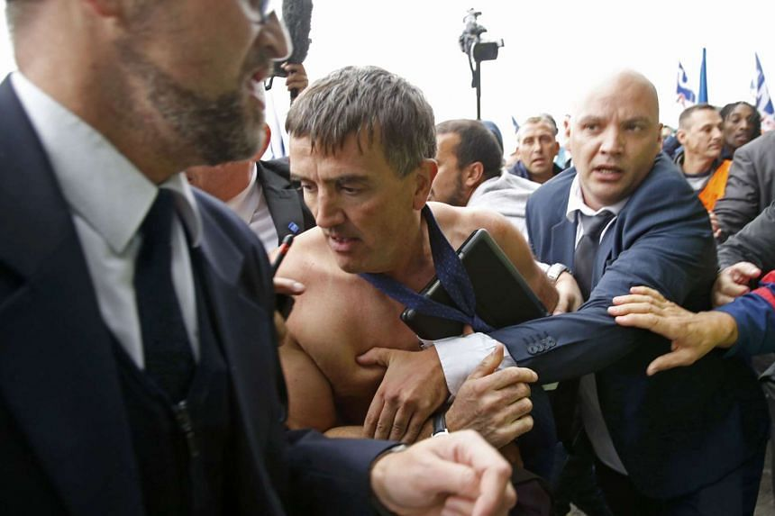 A shirtless Xavier Broseta, Executive Vice-President for Human Resources and Labour Relations at Air France, is evacuated by security after employees interrupted a meeting with representatives staff at the Air France headquarters building at the Char