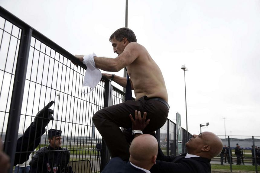 Human Resources Assistant Manager of Air France Xavier Broseta, shirtless, tries to cross a fence, helped by security and police officers, after several hundred of employees invaded the offices of Air France, interrupting the meeting of the Central C