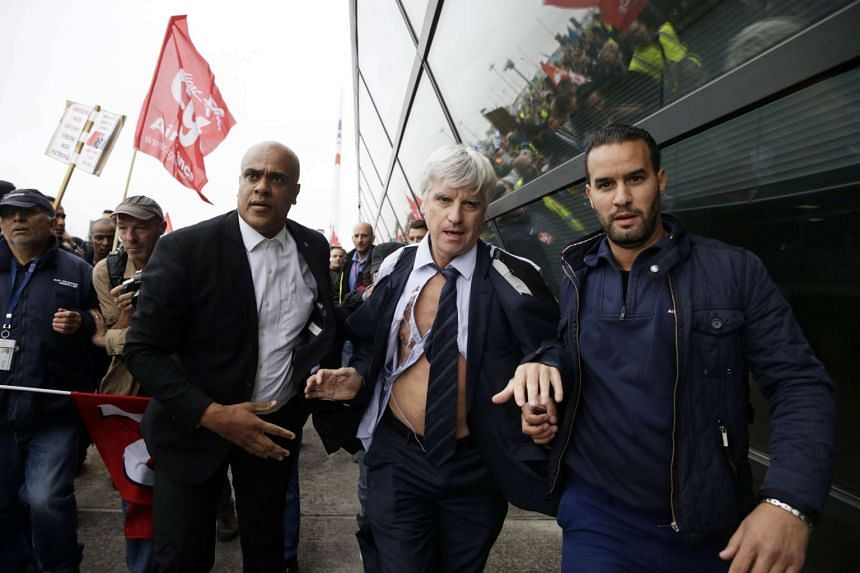 Director of Air France in Orly Pierre Plissonnier, nearly shirtless, runs away from the demonstrators, helped by security officers, after several hundred of employees invaded the offices of Air France, interrupting the meeting of the Central Committe