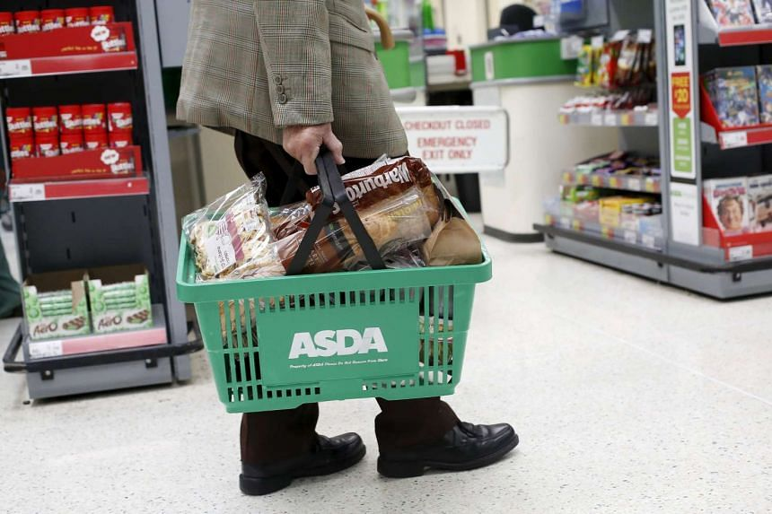 A man carries a shopping basket in an Asda store in north-west London on Aug 18, 2015.