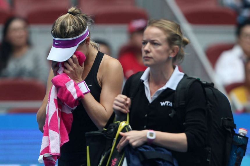 Eugenie Bouchard of Canada cries into her towel after she withdrew from her match against Andrea Petkovic of Germany at the China Open on Oct 5, 2015.